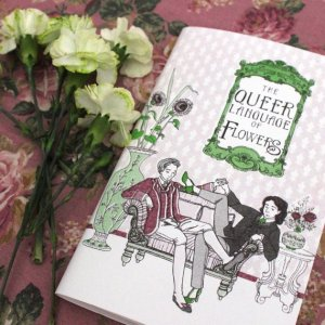 Image of a copy of The Queer Language of Flowers next to some green carnations. Two light-skinned people are sitting on a divan. One has short hair and is wearing a burgundy waistcoat, jacket, and breeches. The other has shoulder-length dark wavy hair and is wearing a green tie, a jacket and trousers, and green heels. There are sunflowers in a vase and roses and lavender in another.