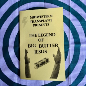 Midwestern Transplant Presents: The Legend of Big Butter Jesus by L.M. Zoller. Photo of a booklet zine printed on yellow paper. There are black and white cutouts of a long stick of butter, the arms of the King of Kings status, and a lightening bolt.